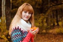 Menina com a xícara de café no parque do outono Fotos de Stock