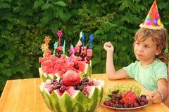 A menina come a fruta no jardim, festa de anos feliz foto de stock