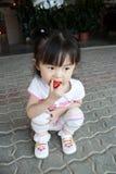 A menina come a morango foto de stock