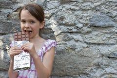 A menina come o chocolate Foto de Stock Royalty Free