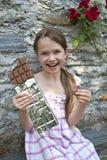 A menina come o chocolate Fotos de Stock