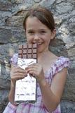 A menina come o chocolate Fotografia de Stock Royalty Free