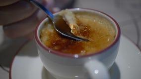 A menina come o creme brulée da sobremesa no café Revestimento do creme brulée pelo cozinheiro chefe, pelo açúcar e pela tocha video estoque