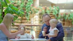 A menina come o gelado um chifre no shopping grande A família come o gelado na alameda Família feliz cute vídeos de arquivo