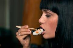 A menina come o sushi Fotografia de Stock