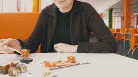 A menina come o sushi Rolls com hashis em um restaurante japonês vídeos de arquivo
