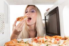 A menina come a pizza fora da microonda imagens de stock