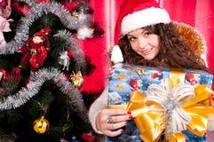 A menina começ um presente de Natal Fotografia de Stock Royalty Free