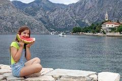 A menina come uma melancia em uma baía de Kotor das férias de verão Imagens de Stock Royalty Free