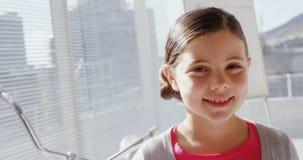 Menina como o executivo fêmea que sorri na câmera no escritório 4k vídeos de arquivo