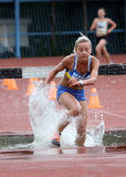 A menina compete no Steeplechase de 3.000 medidores Imagens de Stock Royalty Free
