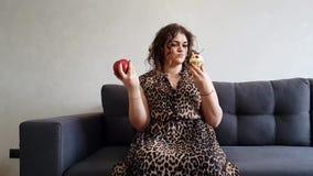Menina completa bonita com maçã e bolo, lento-movimento da escolha da emoção filme