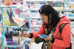A menina compra cosméticos na loja imagens de stock royalty free