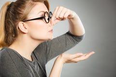 A menina comprime seu nariz devido ao fedor do fedor fotografia de stock royalty free