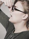 A menina comprime seu nariz devido ao fedor do fedor Fotos de Stock Royalty Free