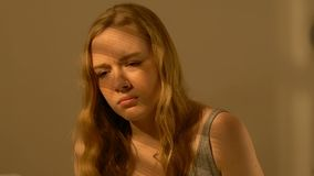 Menina comprimida do adolescente que senta-se apenas na sala, idade inábil, vítima tiranizando vídeos de arquivo