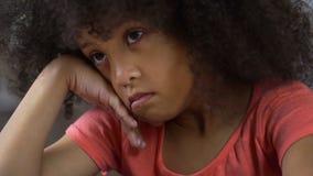Menina comprimida que senta-se apenas e que pensa sobre seu comportamento, punição fotografia de stock