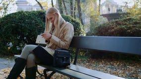 A menina comunica-se em um smartphone em um parque da cidade em um banco vídeos de arquivo