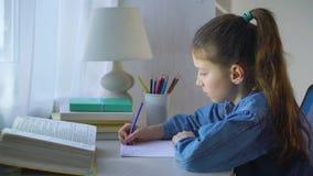 Menina concentrada da escola no revestimento das calças de brim que faz trabalhos de casa na folha de papel vídeos de arquivo