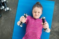 Menina concentrada que encontra-se na esteira e que exercita com pesos imagem de stock