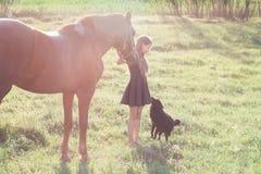 A menina conduz seu cavalo e afago do cão preto Imagens de Stock Royalty Free