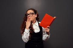 Menina confusa com o livro sobre a obscuridade Imagens de Stock