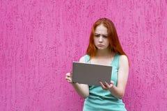 Menina confusa do ruivo que usa o PC da tabuleta fotos de stock