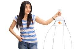 Menina confusa que guarda um peixe dourado no saco com escape da água fotografia de stock