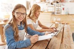 Menina consciente esperta que ajuda sua mamã no café da família fotografia de stock royalty free
