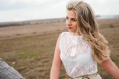 A menina considerável do indivíduo e do louro que anda no campo, um homem conduz uma mulher que guarda a mão fotos de stock royalty free