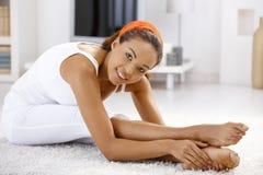 Menina consideravelmente étnica que exercita em casa Fotografia de Stock Royalty Free