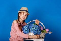Menina consideravelmente adolescente com uma cesta das flores Fotos de Stock