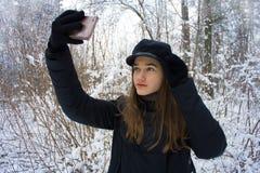 A menina consideravelmente adolescente da forma faz o retrato do selfie na floresta nevado do inverno foto de stock