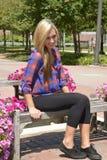 Menina consideravelmente adolescente que senta-se em um banco de madeira Fotografia de Stock Royalty Free