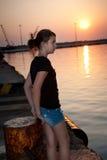 Menina consideravelmente adolescente que senta-se em uma doca que olha no th Fotografia de Stock