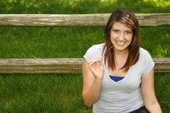 Menina consideravelmente adolescente que sorri fora pela cerca Imagens de Stock