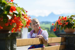 Menina consideravelmente bávara com as flores na exploração agrícola Cumes no backgrou Fotos de Stock