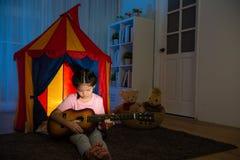 Menina consideravelmente doce que guarda a guitarra pequena Fotos de Stock