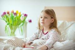 Menina consideravelmente doente da criança pequena que coloca no chá da bebida da cama fotos de stock royalty free