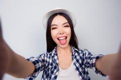 A menina consideravelmente encantador na roupa ocasional e no chapéu está tomando um auto imagens de stock royalty free