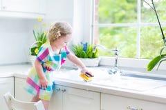 Menina consideravelmente encaracolado da criança em pratos de lavagem do vestido colorido fotos de stock