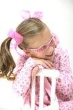 Menina consideravelmente loura com os vidros cor-de-rosa que sentam-se na corrente alternada Foto de Stock Royalty Free