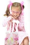 Menina consideravelmente loura com os vidros cor-de-rosa que sentam-se na corrente alternada Fotografia de Stock