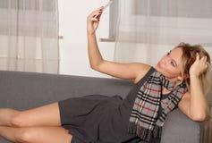 Menina consideravelmente loura do estudante que toma o autorretrato com telefone esperto foto de stock royalty free