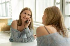 Menina consideravelmente loura dos jovens que fala no telefone na frente de um espelho foto de stock