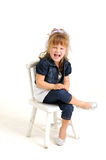 A menina consideravelmente loura no vestido azul veste-se na cadeira Fotos de Stock