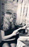 Menina consideravelmente loura que lê um livro imagens de stock