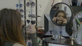 Menina consideravelmente nova do adolescente que tenta vários tipos dos óculos de sol em uma loja - filme