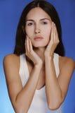 A menina consideravelmente saudável com pele limpa toca em sua face no fundo azul Imagem de Stock Royalty Free