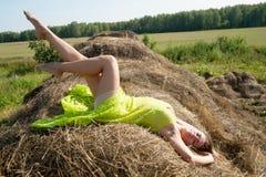 A menina consideravelmente 'sexy' relaxa no feno Fotos de Stock